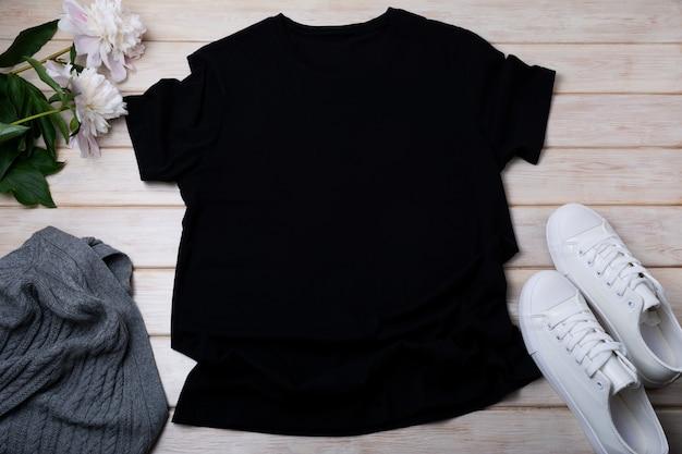 Мокап черной женской хлопковой футболки с серым свитером из арана, белыми кроссовками и бледно-розовым пионом. дизайн шаблона футболки, макет презентации с принтом футболки