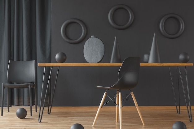 Black and wood dining room interior with hairpin table, two chairs and handmade sculptures