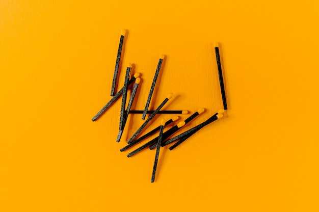 Black wood matches with yellow heads on bold yellow background.