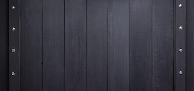 Черный деревянный фон как поверхность текстуры с винтами