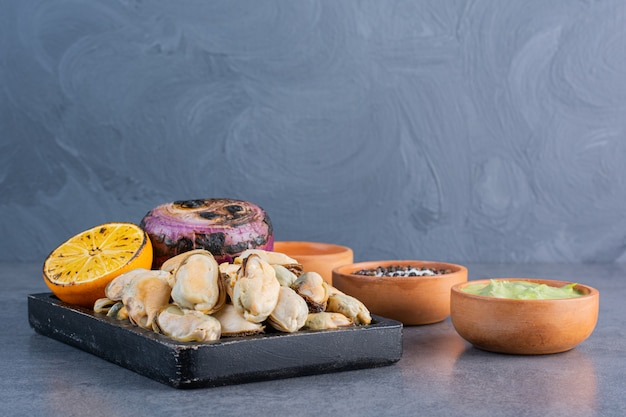 A black wooden board of cooked shells with fried onion and sliced lemon on a stone surface