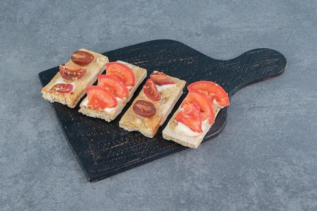Una tavola di legno nera di crostini croccanti con pomodori.