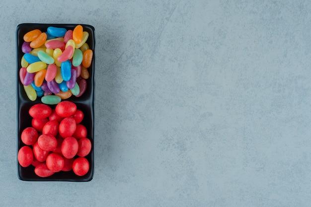 Una tavola di legno nera piena di caramelle colorate di fagioli su una superficie bianca