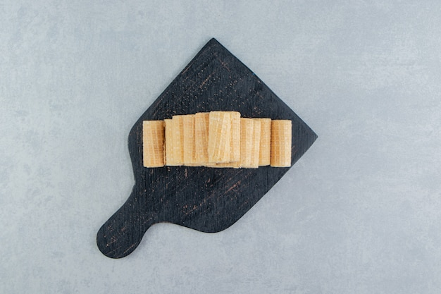 A black wooden board full of crusty waffle rolls.