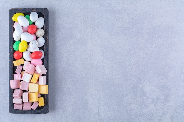 Una tavola di legno nera piena di caramelle colorate zuccherine. foto di alta qualità Foto Gratuite
