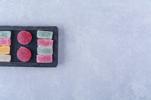 Una tavola di legno nera piena di caramelle colorate zuccherine. foto di alta qualità