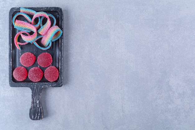 A black wooden board full of sugary colorful candies.