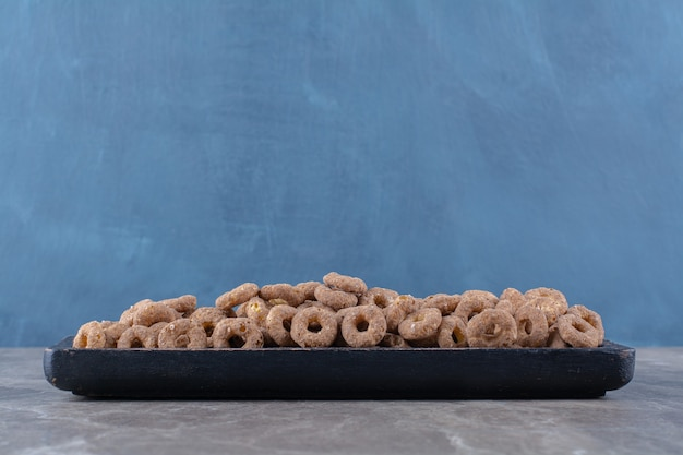 A black wooden board of healthy chocolate cereal rings for breakfast .