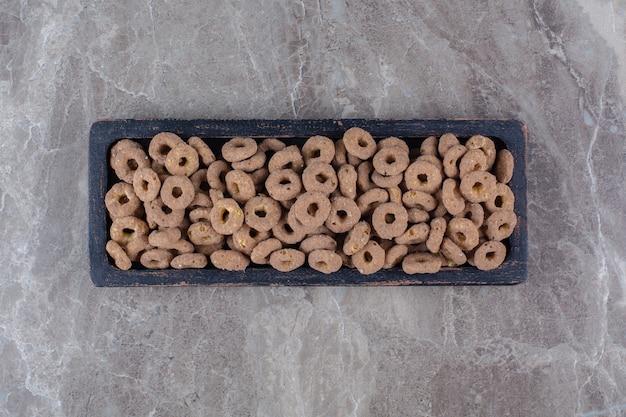 Una tavola di legno nera di anelli di cereali al cioccolato sani per la colazione.