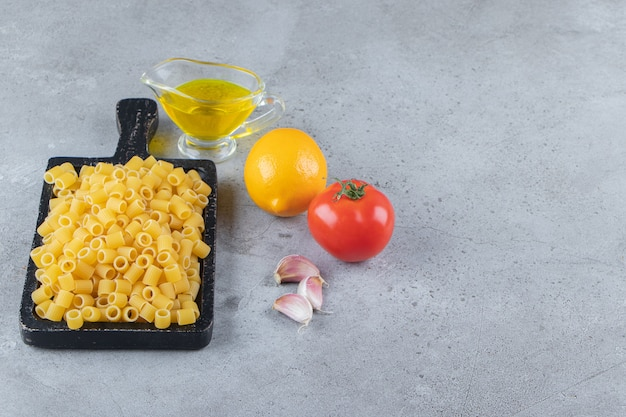 A black wooden board of raw dry ditali rigati pasta with fresh red tomato and oil.