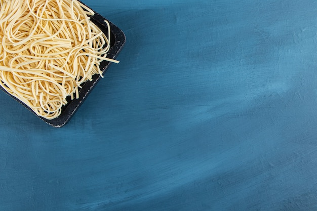 A black wooden board of raw noodles on a blue background.