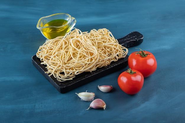 Una tavola di legno nera di spaghetti crudi su sfondo blu.