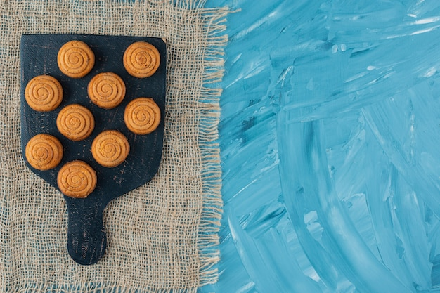 Una tavola di legno nera di biscotti rotondi deliziosi dolci su una tela di sacco.