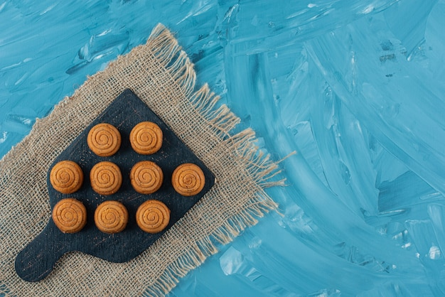 A black wooden board of sweet delicious round cookies on a sackcloth