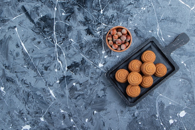 A black wooden board of sweet fresh round cookies for tea with healthy nuts on a marble background .