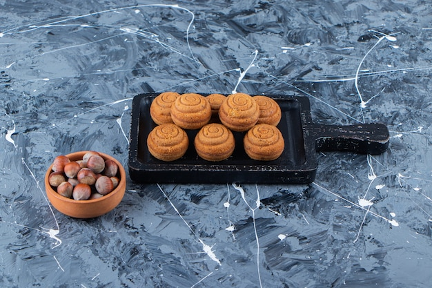 A black wooden board of sweet fresh round cookies for tea with healthy nuts on a marble surface .