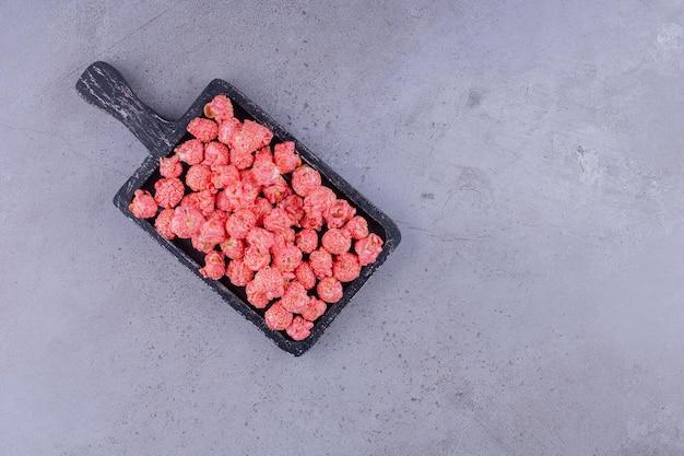 Tavola di legno nera con caramelle popcorn rosse su sfondo marmo. foto di alta qualità