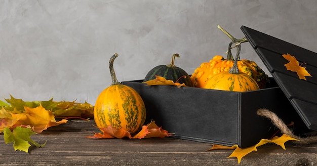 Black wooden box with orange pumpkins on a wooden table with maple leaves.