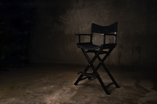 A black wooden chair stands in a photo studio against the background of an old, scratched concrete wall.