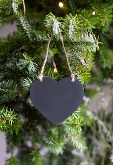 Черное деревянное сердце на зеленом фоне еловых веток. рождественский новогодний состав. прикоснись, скопируй место на день святого валентина.