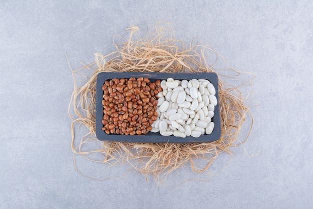 Черная деревянная тарелка, помещенная на груду соломы, наполненная красной фасолью и темно-синей фасолью на мраморной поверхности