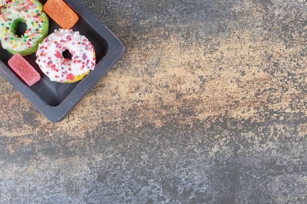 木製の表面に一口サイズのドーナツとマーマレードが付いた黒い木製の大皿