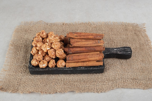 Vassoio di legno nero su un pezzo di tessuto con pile di caramelle popcorn e tagli di cannella su marmo.
