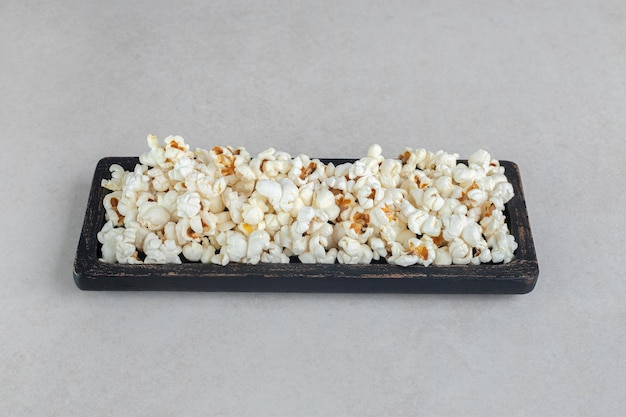Black wooden tray with fresh popcorn on marble table.