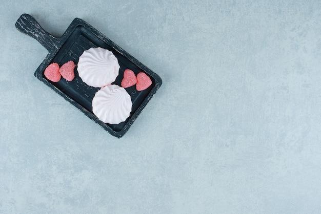 Vassoio in legno nero con marmellate e biscotti su marmo.