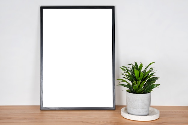 ライトグレーの壁に木製のテーブルの上のコンクリートポットに白い空白のカードと緑の植物と黒い木製の垂直フレーム