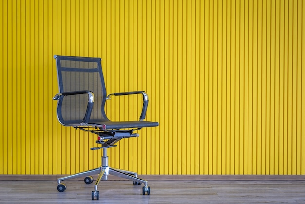 Black working chair with yellow wall on wooden floor.