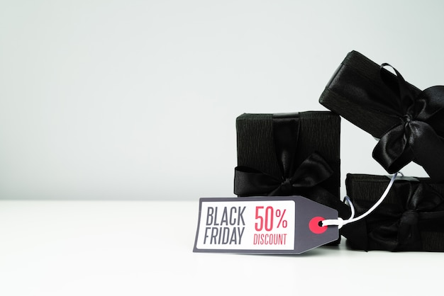 Black wrapped gifts with tag on plain background