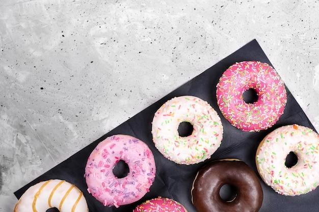 Черная упаковочная бумага с цветными традиционными пончиками лежит по диагонали на сером бетонном фоне с копией пространства.