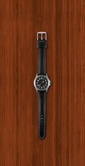 Black wrist watch isolated on dark wooden background