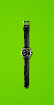 Black wrist watch isolated on green background