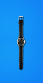 青い背景に分離された黒い腕時計