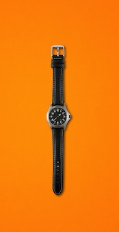 Black wrist watch isolated on orange