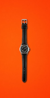 Black wrist watch isolated on red background