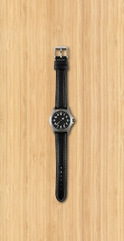 Black wrist watch isolated on wooden