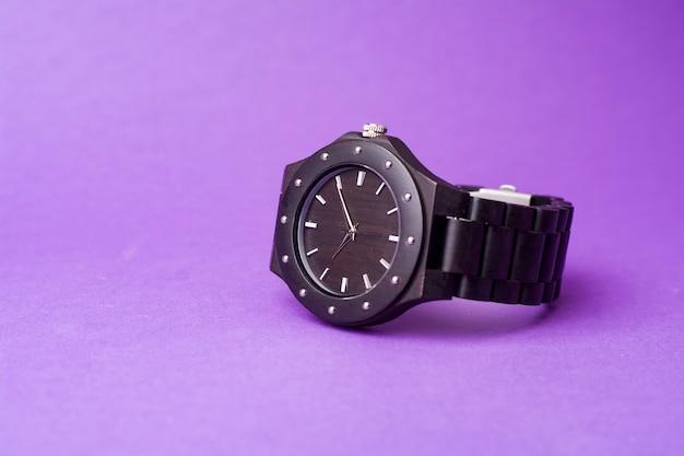 紫色の背景に黒い腕時計