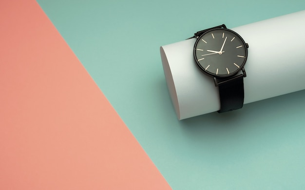 Black wrist watch on white tube on top of light blue and peach color background