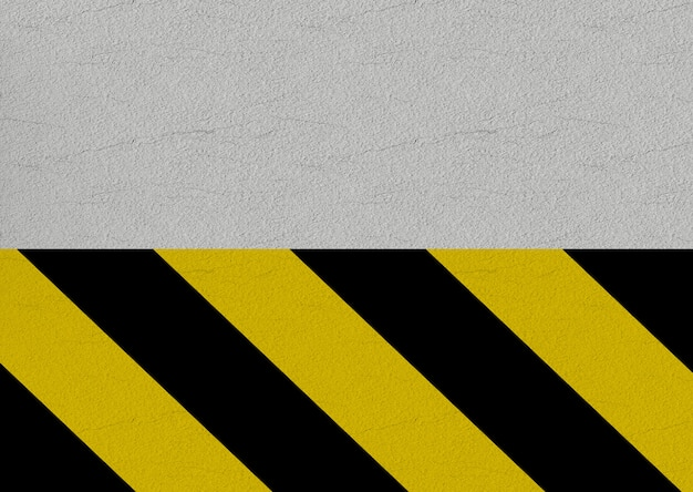 Black and yellow caution line on cement wall background.