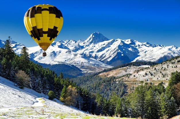 Black and yellow hot air balloon with pic du midi de bigorre  pyrenees