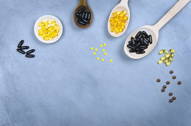 Black and yellow pills and wooden spoon on gray background