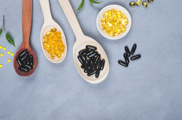 Black and yellow pills on wooden spoon on gray background