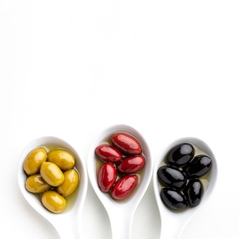 Black yellow red olives in spoons with copy space