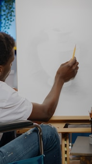 Black young artist with disability creating vase design on canvas while sitting in artwork studio room at home. african american person with handicap in wheelchair drawing masterpiece