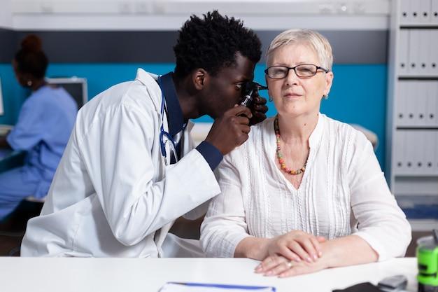 Black young doctor using otoscope on elder patient