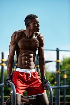 公園の段違い平行棒で運動する黒人の若い男、クロスフィットのコンセプト、スポーツグラウンドで、通りの段違い平行棒で運動をしているアフリカ系アメリカ人の男