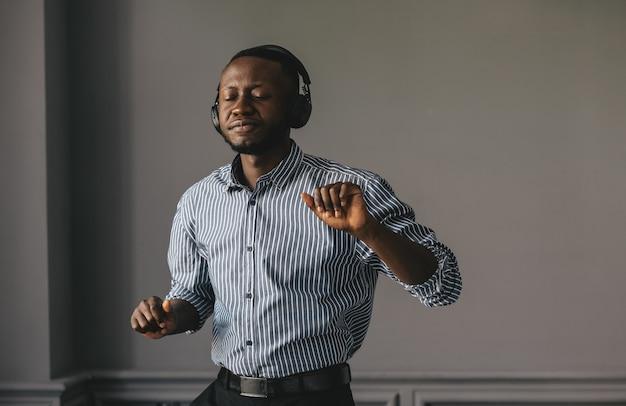 灰色の背景で音楽に合わせて踊るヘッドフォンで黒人の若い男。高品質の写真